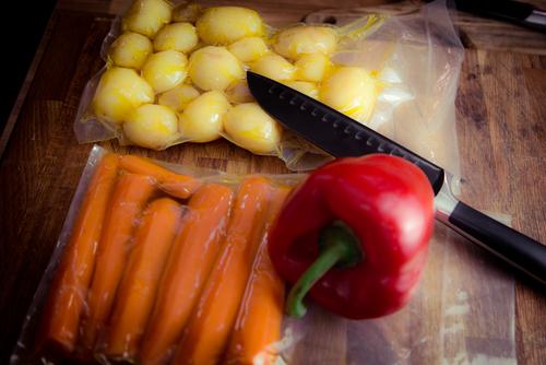 Carottes et pommes de terre sous vide accompagnés d'un couteau et d'un poivron rouge