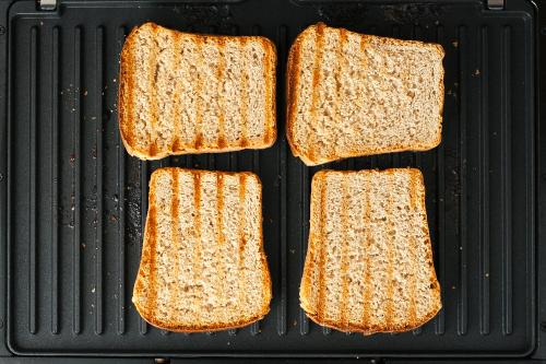 Quatre croque-monsieur cuits et dorés, posés sur une plaque