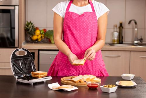 Une femme portant un tablier rose prépare des croque-monsieur dans une cuisine