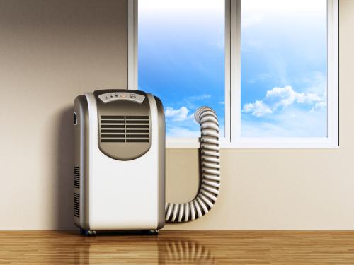Climatiseur mobile monobloc à tuyau simple placé à côté de la fenêtre