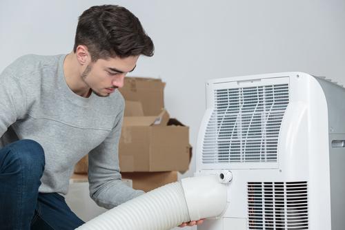 Homme installant un climatiseur mobile