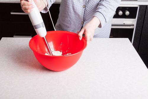 Personne préparant un plat dans un saladier rouge avec un mixeur plongeant