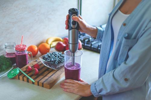 Femme préparant un smoothie avec un mixeur plongeant